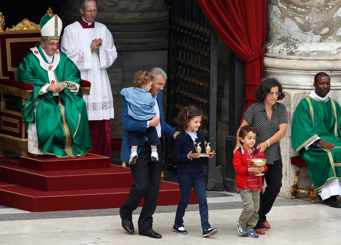 Pope watches as family carries offertory gifts during Mass for catechists in St. Peter's Square at Vatican